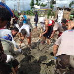 Gawad Kalinga's volunteers working with locals to help rebuild homes